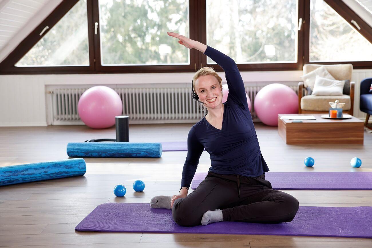 pilates coach anja auer macht uebung in ihrem online pilates kurs auf der matte vor